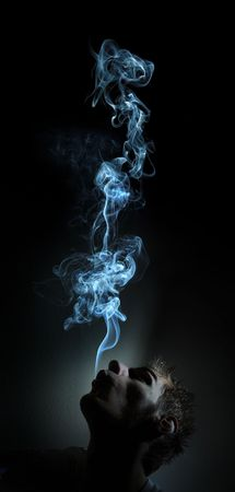Young adult white Caucasian man smokes in a dark room. The smoke is glowing against the black background