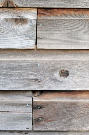 nailed: This brown wooden wall is cheap and has nails in it.
