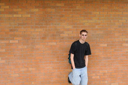 A tall white Caucasian young adult teenage male stands in front of a brick wall. Lots of room for your copyspace text. He has a backpack and glasses 免版税图像