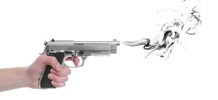 A hand gripping a pistol grip hand gun isolated on white background with black smoke with copyspace with room for your text photo