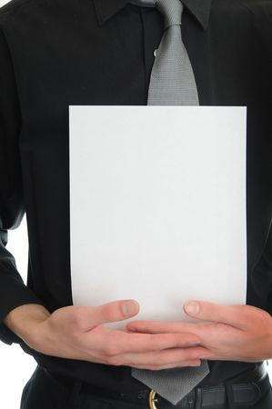 Young adult man in black suit and tie holds a white blank piece of paper. photo