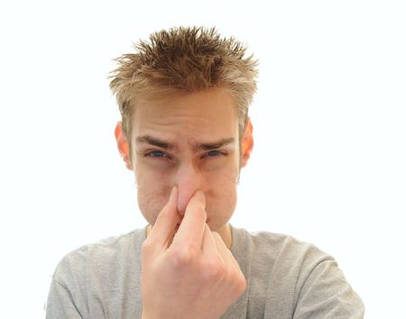 odor: Young adult man tightly holds his hand over his nose in order to plug out the horrible odor he is smelling. Isolated on white background with room for your copyspace text.