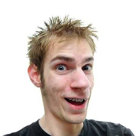 grins: An average looking young adult smiles and grins at the camera. He has braces and green eyes with spiky hair Stock Photo