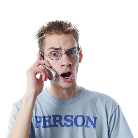 angry teenager: Young 18 year old adult teenager talks on his miniature 3G cellular phone isolated on white background. His shirt says Person