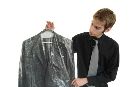 cleaned: Young man holds newly dry cleaned business jacket coat
