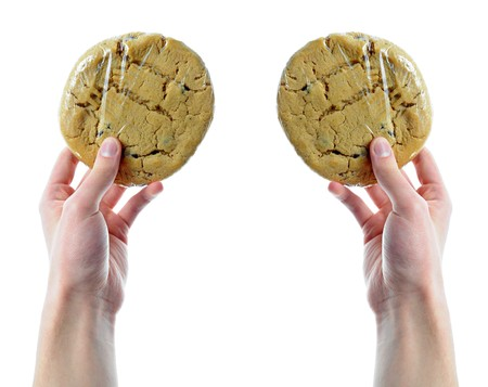 shrink wrapped: Two hands holding two cookies that are in shrink wrap isolated on a white background