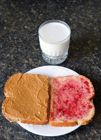 Open peanut butter and jelly sandwich on a counter top with a glass of milk beside the plate photo