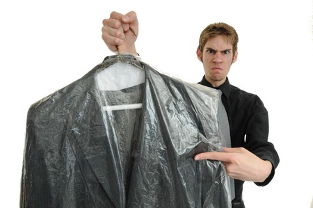 unsatisfied: Unsatisfied customer holds up a dry cleaned suit. Missed a spot! Stock Photo