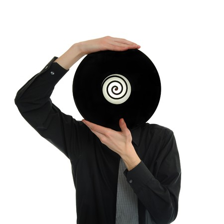 Man in suit and tie holds up a record LP to his head Stock Photo