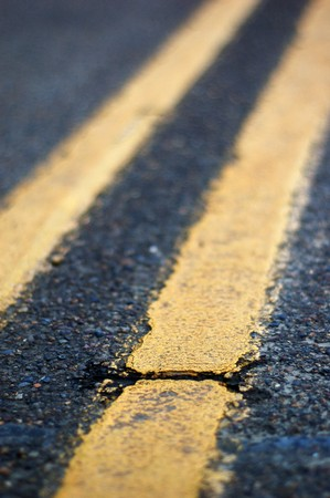 imperfection: Crack in a double yellow lined road with shallow depth of field.