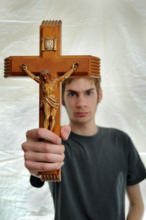 holding close: Young man holds up a wooden crucifix of Jesus.
