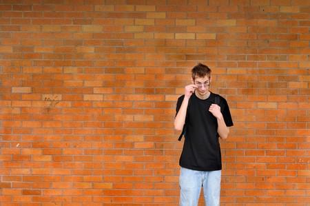 Un alto bianco caucasica giovane adolescente maschio adulto si trova di fronte un muro di mattoni tirando giù gli occhiali. Sacco di spazio per il testo di copyspace. Egli suo indossando uno zaino