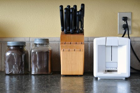 counter top: Kitchen counter top with coffee jars, knife set, and toaster