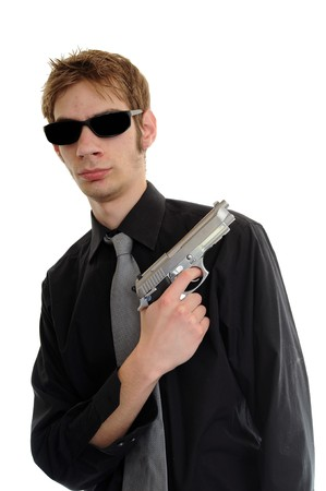 aviators: Young man holding up a gun with the focus on his face. He is wearing sunglasses. Stock Photo