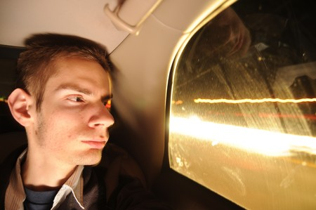 Young man looks out the car window at night with car lights zooming by.