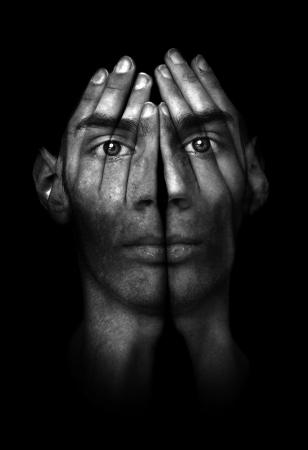 Retrato oscuro surrealista de un hombre joven que cubre su rostro y los ojos con sus manos, pero él puede ver a través de ellos.