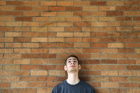 Young caucasian male looks up above his head leaning against a brick wall.