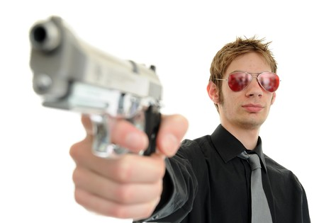 Young man holding up a gun with the focus on his face. He is wearing sunglasses and is isolated on white background cutout.