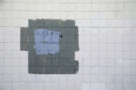 Tiled wall with a blank white bricks and gray spray painted graffiti. Stock Photo - 7036581