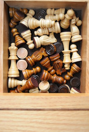 chess board: A bunch of chess pieces thrown into a wooden chess board container. Stock Photo