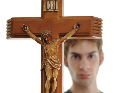 Young man holds up a wooden crucifix of Jesus. Isolated on white. photo