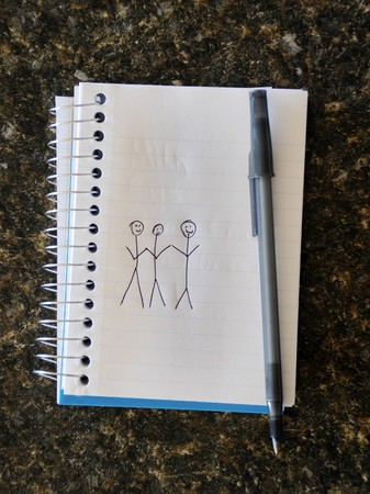 Stick figure drawing of three people holding hands on a notepad. photo