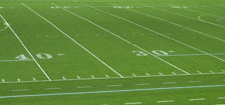 A stadium view of an American football field lines on artifical green turf.