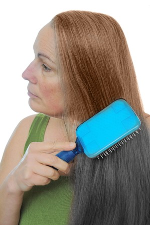 tinge: Woman combs her hair gray to brown showing the signs of old age and youth Stock Photo