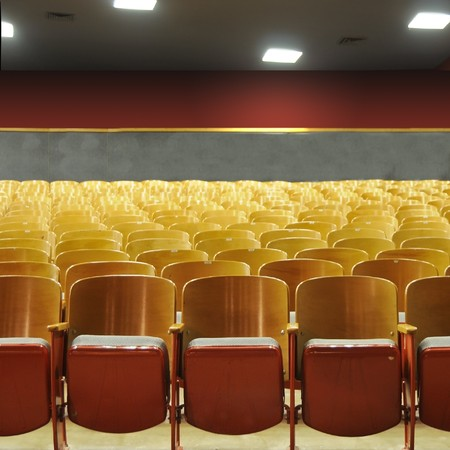 Several rows of theater seats in an auditorium with lights above. photo