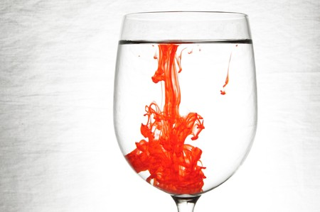 dye: A drop of red liquid was just poured into a clear wine glass.