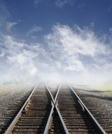 railway station: Two railroad tracks lead off into the daylight foggy sky with clouds.