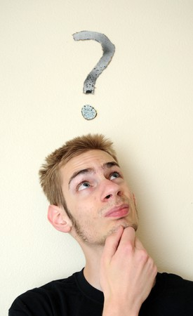 Young white Caucasian male wondering with a question mark above his head on the wall behind him. Focus point is on the person. photo