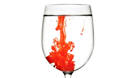 ink in water: A drop of red liquid was just poured into a clear wineglass.
