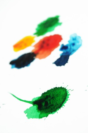 dabs: Abstract closeup photograph of colorful ink and paint splotches, splatters, dabs, dribbles, and splatters isolated on a white background. Shallow depth of field.