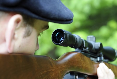 rifle: Man looking through the scope on his wooden rifle gun