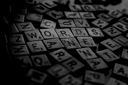 imprinted: A bunch of scrambled game board pieces with letters imprinted on them, focusing on Words with a shallow depth of field.