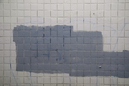 Tiled wall with a blank white bricks and gray spray painted graffiti. Stock Photo - 7216258