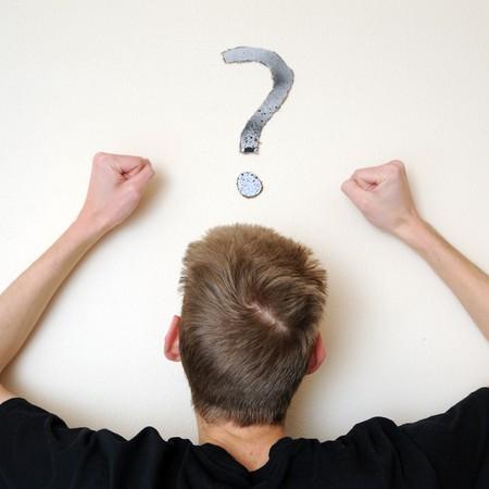 若い白人男性大人前方を見つめて、混同して、壁に彼の頭の上に疑問符の付いた白い。フォーカス ポイントは、人の頭の上です。 写真素材