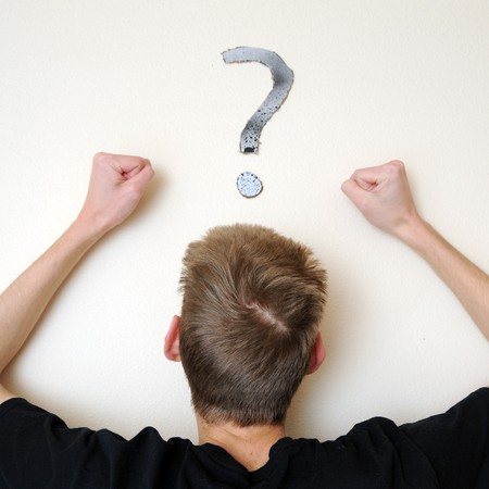 Young white Caucasian male adult staring forward, confused, with a question mark above his head on the wall. Focus point is on the persons head.