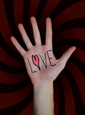 amorousness: The word love written on a teenagers white Caucasian hand isolated on black background.