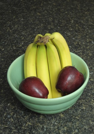 kitchen counter top: A bunch of bananas and apples inside of a fruit bowl resting on a black kitchen counter top. Stock Photo