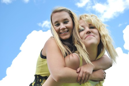 Two beautiful, attractive, happy, carefree blond teenage girls giving each other a piggyback ride in the sunshine with clouds over a blue sky in the background. photo