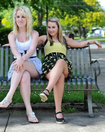 Two girl friends sitting on a metal bench, smiling at the camera. They can be seen as being flirtatious, happy or welcoming.  Stock Photo - 7214019