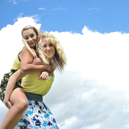Two beautiful and attractive blond teenage girls giving a piggyback ride in the sunshine with clouds and sky in the background.