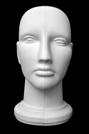 mannequin head: Front view of a mannequin dummy head isolated on a black background.