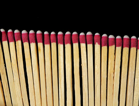 pyromania: A bunch of wooden matches isolated on a black background