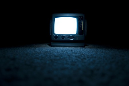 A miniature portable TV screen on at night on the floor with a white screen glowing