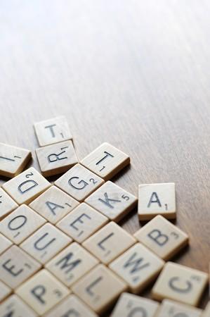 Een stelletje vervormd spelbord stukken met letters op hen.  Stockfoto