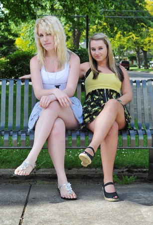 Two girl friends sitting on a metal bench, smiling at the camera. They can be seen as being flirtatious, happy or welcoming. Stock Photo - 7276853