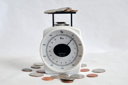 A bunch of coins and change on a weighing scale. Stock Photo - 7276843